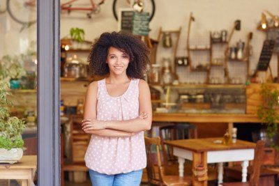 small business owner standing in front of her store