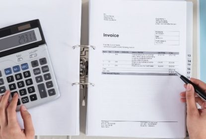 person managing a binder of invoices